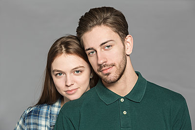 Portrait of smiling couple standing against gray background - p301m1406601 by Vladimir Godnik