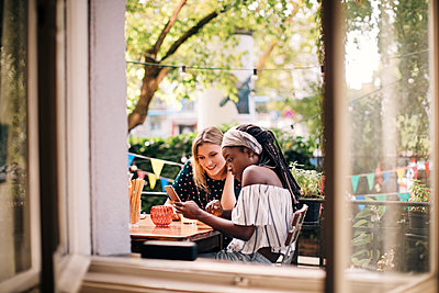 Multi-ethnic female friends looking at mobile phone seen through window - p426m2046266 by Maskot