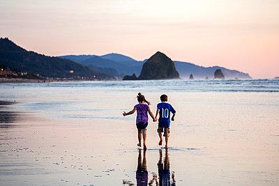 Caucasian children walking on beach - p555m1413211 by Adam Hester
