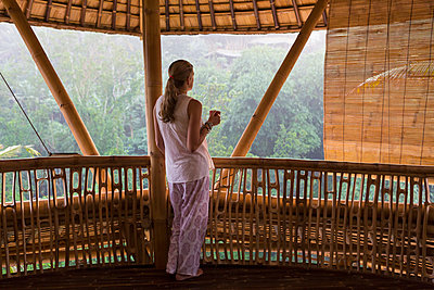 Caucasian woman overlooking view from balcony - p555m1419678 by Marc Romanelli