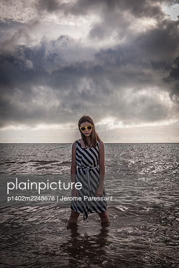 Mädchen mit Sonnenbrille steht im Meer - p1402m2248676 von Jerome Paressant