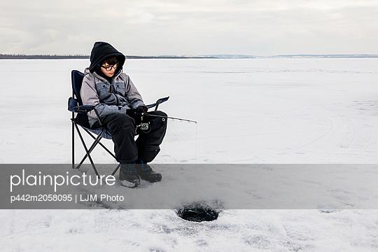 Boy Patiently Waiting For A Bite While Ice Fishing At Wabamun Lake; Wabamun, Alberta, Canada - p442m2058095 by LJM Photo