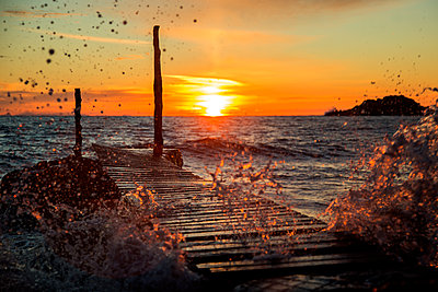 Ibiza Sunset With Waves crashing on dock - p1166m2090641 by Cavan Images
