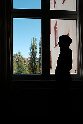 Silhouette of young woman at the window, shutdown due to Covid-19 - p1229m2178858 by noa-mar