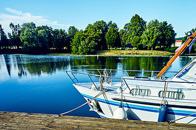 Boat on a jetty on the canal - p1312m2103825 by Axel Killian