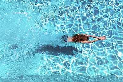 Woman diving underwater in swimming pool - p300m1166431 by Scott Masterton