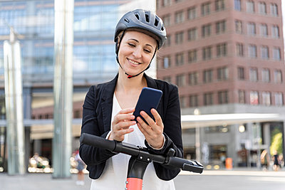 Woman with e-scooter using smartphone in the city, Berlin, Germany - p300m2156872 by William Perugini