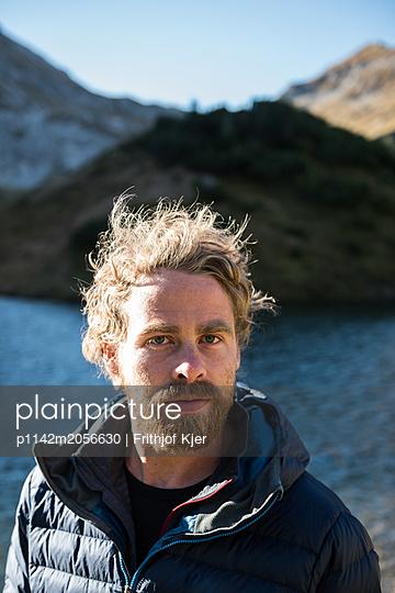 Portrait eines jungen Mannes vor Bergsee - p1142m2056630 von Runar Lind