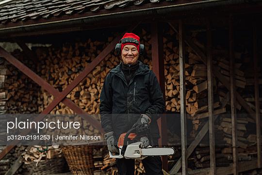 Senior woman holding chainsaw - p312m2191253 by Jennifer Nilsson