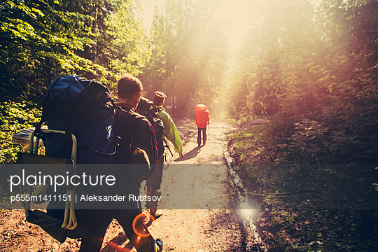 Backpackers hiking on dirt path in forest - p555m1411151 by Aleksander Rubtsov