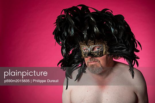 Mann mit nacktem Oberkörper trägt Federn auf dem Kopf und eine Maske - p590m2015835 von Philippe Dureuil