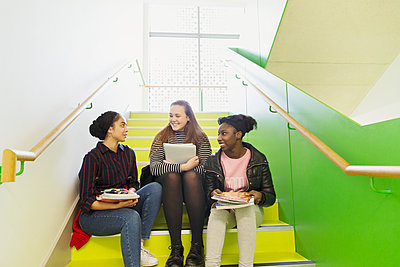 High school girls talking on stairs - p1023m2017331 by Rob Daly