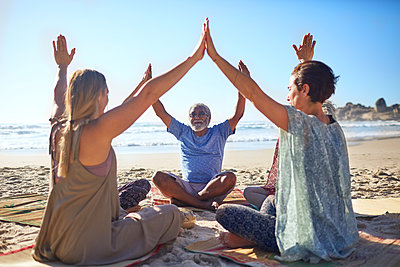 Group joining hands in circle on sunny beach during yoga retreat - p1023m2067358 by Trevor Adeline