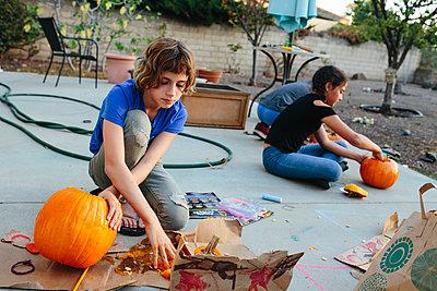 Three kids carve pumpkins outside - p1166m2078345 by Cavan Images