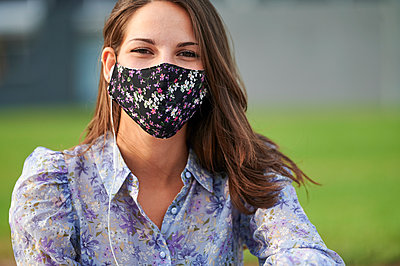 Woman wearing protective face mask while sitting in city - p300m2221524 by Kiko Jimenez