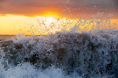 Foam wave splashing with orange sky in background - p343m1475707 by Sean Davey