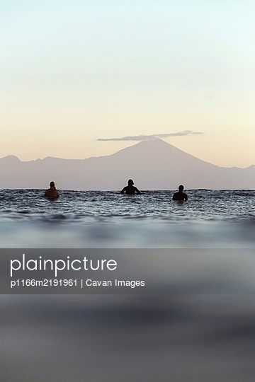 Surfers on surfboard on the sea waiting for a wave, Volcano Rinjani - p1166m2191961 by Cavan Images