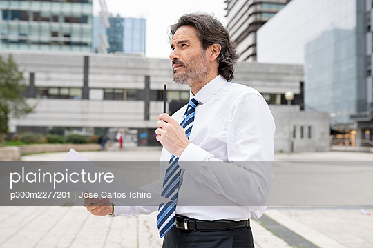 Thoughtful male architect looking away while holding blueprint in office park - p300m2277201 by Jose Carlos Ichiro