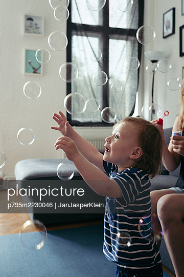 Toddler playing with soap bubbles at home - p795m2230046 by JanJasperKlein