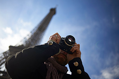 Low angle view of man photographing through DSLR camera against Eiffel Tower and blue sky - p1166m1542243 by Cavan Social