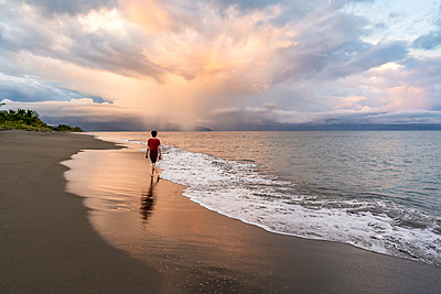 Teenager walking on beautiful beach at sunset - p1166m2189660 by Cavan Images