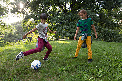 Two boys playing soccer in a park - p1211m1526114 by Danny Weiss