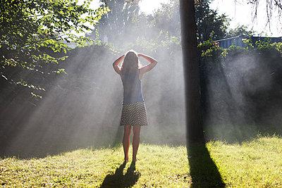 Woman standing in beam of light - p1231m1171263 by Iris Loonen