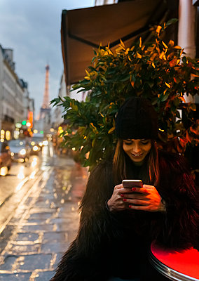 France, Paris, young woman looking at cell phone with the Eiffel Tower in the background - p300m1206299 by Marco Govel