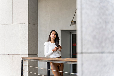 Young woman holding smartphone on balcony - p300m2166200 by VITTA GALLERY