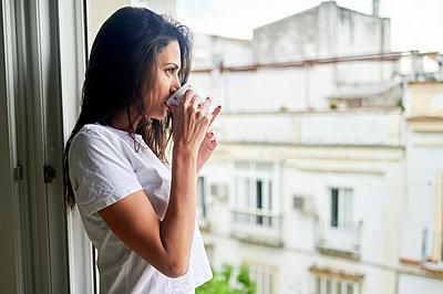 Thoughtful woman looking through window while drinking coffee at home - p300m2282130 by Kiko Jimenez