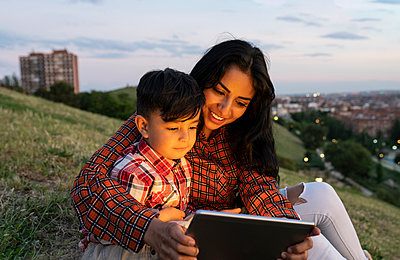 mom with son watching the city at sunset from a hill, Madrid / Spain - p300m2287573 von Jose Carlos Ichiro
