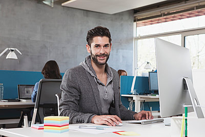 Portrait of smiling man at his workplace in the office - p300m948733f by Rainer Berg
