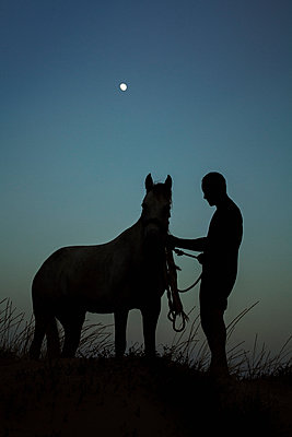 Silhouette man standing with horse on field against blue sky at dusk - p301m1534965 by Isabella Ståhl