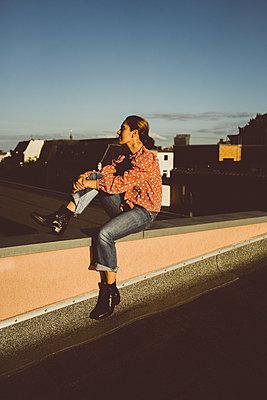 Frau sitzt auf Hausdach - p432m2203186 von mia takahara