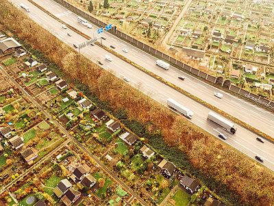 Schnellstraße neben Schrebergärten, Luftaufnahme - p586m1092039 von Kniel Synnatzschke