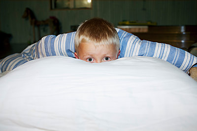 Boy Peeking Through Bed Sheet  - p847m1529363 by Mikael Andersson