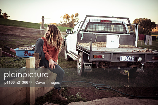 young man with long hair and beard sits on fence by farm truck - p1166m2136677 by Cavan Images