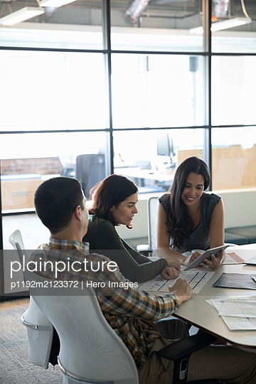 Business colleagues discussing in meeting with tablet - p1192m2123372 by Hero Images