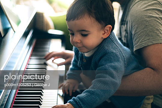 Child and his father playing piano - p300m1205253 by George J