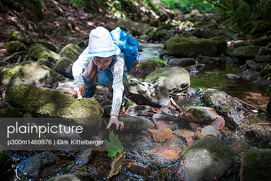 Little girl playing at brook in the woods - p300m1469976 by Dirk Kittelberger
