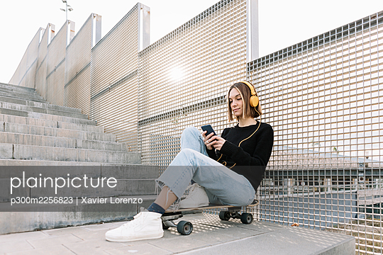 Young woman sitting on skateboard and listening to music outdoors - p300m2256823 by Xavier Lorenzo