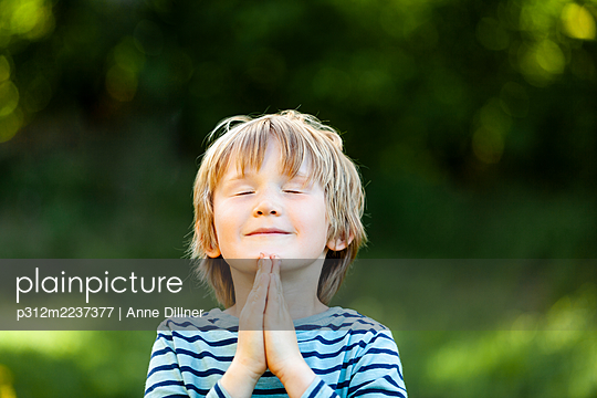 Boy praying with eyes closed - p312m2237377 by Anne Dillner