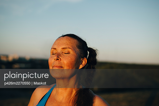 Sportswoman with eyes closed against sky during sunset - p426m2270550 by Maskot