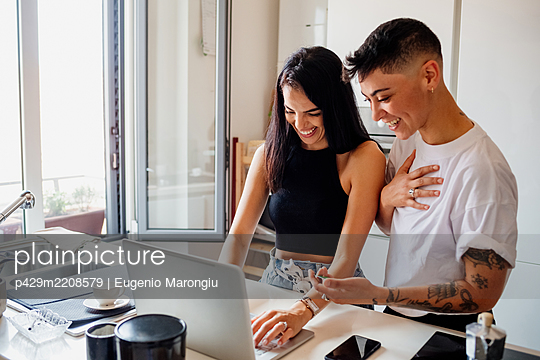 Young lesbian couple standing in kitchen, using laptop. - p429m2208579 by Eugenio Marongiu
