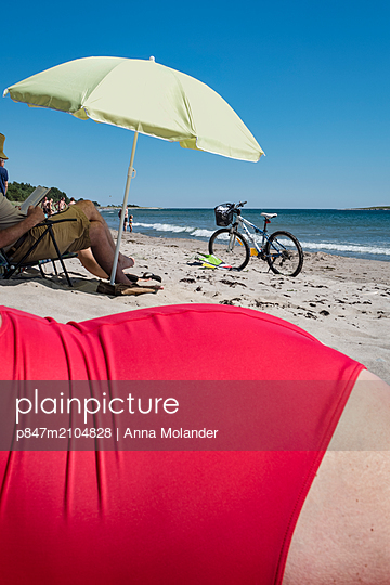 Woman With Red Bathing Suit Sunbathing On Beach, Sweden   - p847m2104828 by Anna Molander