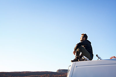 Side view of man sitting on camper van against clear sky - p1166m1231452 by Cavan Images