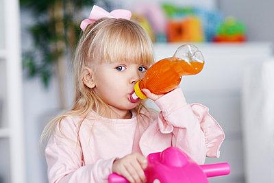 Portrait of blond little girl drinking juice - p300m1580802 by gpointstudio