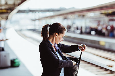 Mature businesswoman searching in bag at train station - p426m2146090 by Maskot
