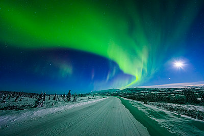 The moon and aurora shine in the night sky over a snow covered Richardson Highway south of Delta Junction; Alaska, United States of America - p442m1448950 by Steven Miley