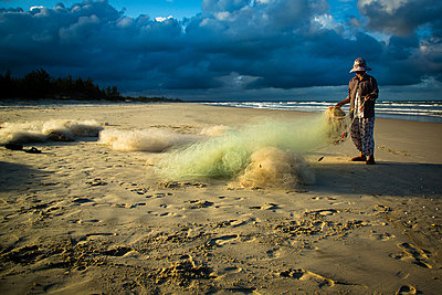 Fisherman organizes his netting on Cua Viet Beach - p934m1022348 by Francis Roux photography